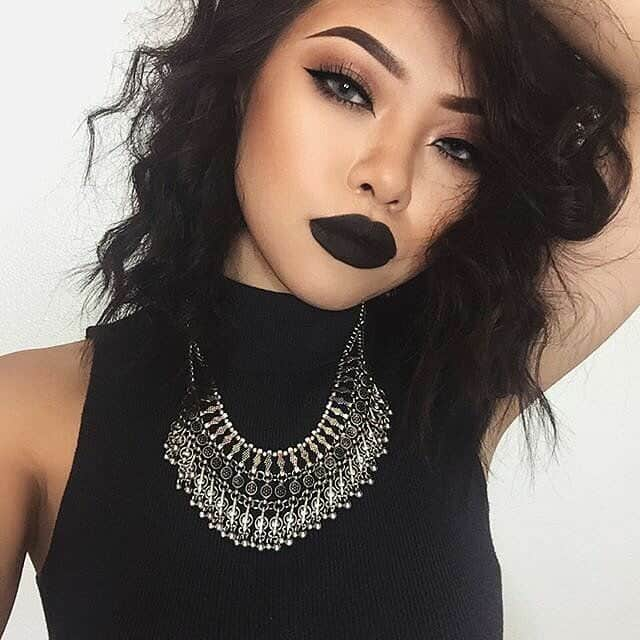 women with black dress and bold makeup